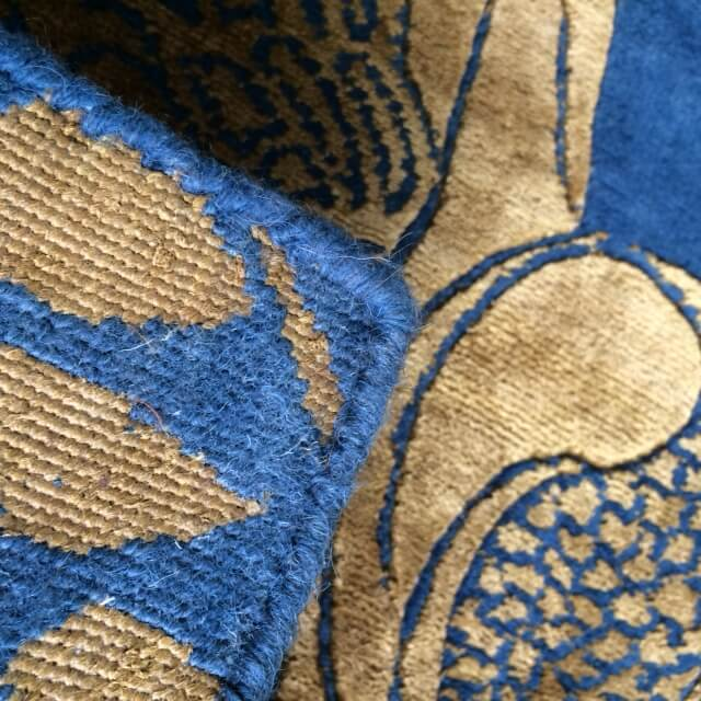 The underside of a rug shows the hand knotting.