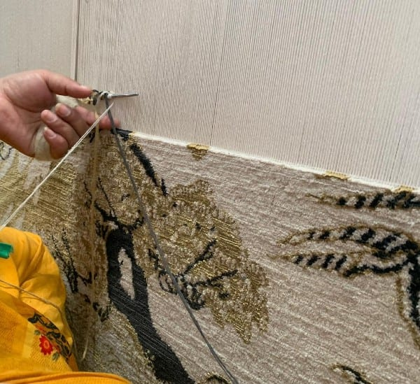 Weaving of a hand knotted rug on a loom